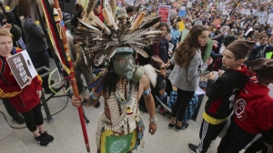 """In this Dec. 2, 2017, photo, a supporter of the Bears Ears and Grand Staircase-Escalante National Monuments wears a colorful headdress during a rally against President Trump's reduction of two National Monuments in Salt Lake City. President Donald Trump's rare move to shrink two large national monuments in Utah triggered another round of outrage among Native American leaders who vowed to unite and take the fight to court to preserve protections for lands they consider sacred."" (AP Photo/Rick Bowmer)"